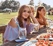 Group of happy girlfriends sitting at the table together celebrating a birthday at the outdoor park. stock photos