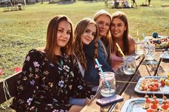 Group of happy girlfriends sitting at the table together celebrating a birthday at the outdoor park. royalty free stock photography