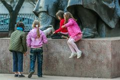 Group of girls and a dog playing around monument in the park. 2010.04.11, Moscow, Russia. Group of girls and a dog playing around monument in the park royalty free stock images