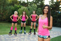 Group of girls doing exercises in kangoo jumping boots. outdoor fitness workout. One girl smiles at looks in camera. Group of girls doing exercises in kangoo royalty free stock images
