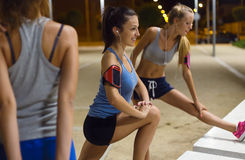 Group of girls doing stretching at night. Royalty Free Stock Images