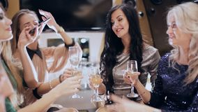 Group of girls drinking champagne in a limousine stock video