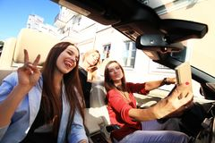 Group of girls having fun in the car and taking selfies with camera. Group of girls having fun in the car and taking selfies with camera Royalty Free Stock Images