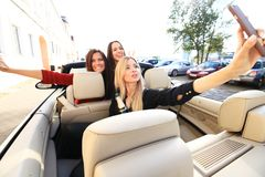 Group of girls having fun in the car and taking selfies with camera. Group of girls having fun in the car and taking selfies with camera Stock Photos