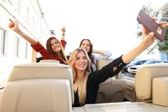 Group of girls having fun in the car and taking selfies with camera. Group of girls having fun in the car and taking selfies with camera Royalty Free Stock Image
