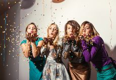Group of girls having a party. With confetti and balloons royalty free stock photography