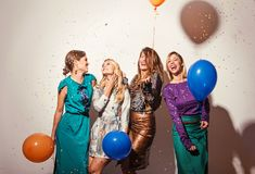 Group of girls having a party. With confetti and balloons royalty free stock image