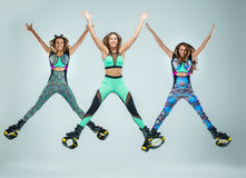 The group of girls, jumping on kangoo training. The group of young girls, jumping on kangoo training on gray Stock Images