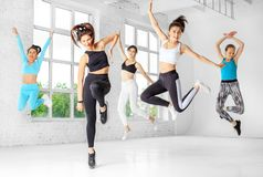 A group of girls jumping to dance in the dance class. The concept of sports, a healthy lifestyle, fitness, stretching and dancing.  royalty free stock photo