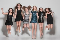 The fashion girls jumping together and looking at camera over gray studio background stock image
