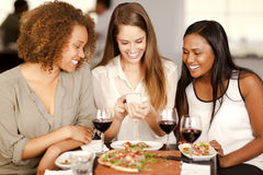 Group of girls looking at a smartphone. Group of mixed-race girls looking at a smartphone in a restaurant Stock Image