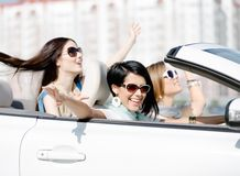 Group of girls with outstretched arms in the car. Group of happy girls with outstretched arms in the car. Little trip of teenage ladies Royalty Free Stock Photo