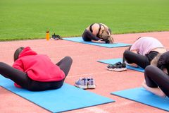 A group of girls performs fitness exercises in the open air. Back view. Exercise for stretching in the lotus position. royalty free stock photography