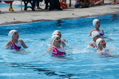 Group of girls in a pool practicing synchronized swimming Stock Images