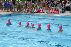 Group of girls in a pool practicing synchronized swimming Stock Image