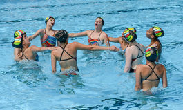 Group of girls in a pool practicing synchronized swimming Royalty Free Stock Photography