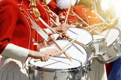 A group of girls in red uniforms playing on white front drums royalty free stock photography
