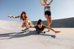 Women riding skateboards and having fun at skate park. Group of girls riding skateboards and having fun at skate park. Happy women friends enjoying skateboarding Royalty Free Stock Photography