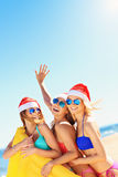 Group of girls in Santa's hats having fun on the beach Stock Photos