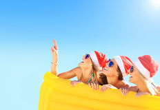 Group of girls in Santa's hats having fun on the beach Stock Images