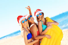 Group of girls in Santa's hats having fun on the beach Stock Photography