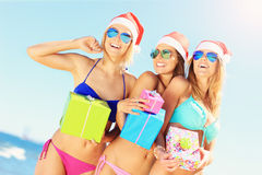 Group of girls in Santa's hats having fun on the beach Stock Image