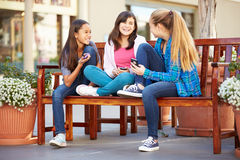 Group Of Girls Sitting In Mall Using Mobile Phones Stock Image