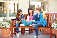 Group Of Girls Sitting In Mall Using Mobile Phones Royalty Free Stock Images