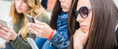 Group of girls with smartphones. Technology isolation and emotional depresion. Group of girls with smartphones. Technology cell phone isolation and emotional royalty free stock images