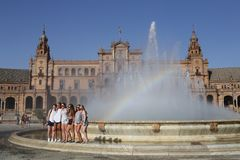Group of girls tourists in the fountain of the Spain Square of Sevilla. In Andalusia southern Spain. A good day ago, the sun shines and there is a rainbow in Stock Image