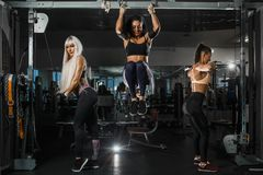 Group of girls is training with TRX straps and upper block parallel grip toi the chest in the gym. They are wearing the. Sportswear. Horizontal stock photo