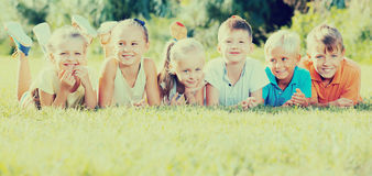 Group of glad kids lying on green grass in park Royalty Free Stock Image