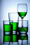 Group of glasse whit green water on blue background. And reflex Royalty Free Stock Photography
