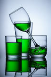 Group of glasse whit green water on blue background. And reflex Stock Images