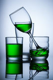 Group of glasse whit green water on blue background. And reflex Royalty Free Stock Image