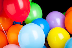 Group of glossy colorful balloons over black wall Royalty Free Stock Images