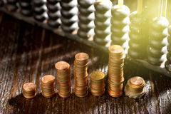 Group of gold coin. Setting in graph form and abacus with studio Lighting stock photo