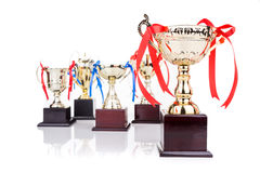 Group of gold trophies with decorative ribbons, focusing on one Royalty Free Stock Photography