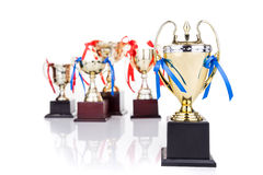 Group of gold trophies with decorative ribbons, focusing on one Stock Images