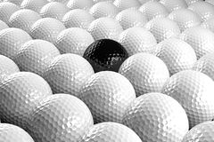 Group of golf balls. 3d White Golf balls & one black in the middle Stock Photo