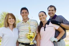 Group Of Golfers Holding Trophy. Group portrait of friends holding winning trophy at golf course Stock Image