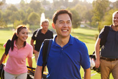Group Of Golfers Walking Along Fairway Carrying Golf Bags royalty free stock photos