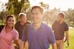 Group Of Golfers Walking Along Fairway Carrying Golf Bags Stock Photography