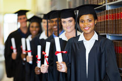 Group of graduates in library. Group of happy graduates holding diploma in library Stock Images