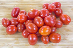 Grape tomatoes on wood cutting board Stock Photo