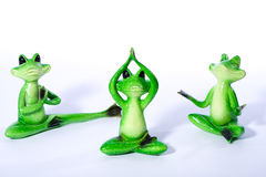 Group of green frog figures stretching and doing yoga exercises Royalty Free Stock Photo