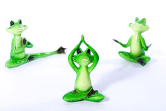 Group of green frog figures stretching and doing yoga exercises Royalty Free Stock Images