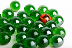 Group of green glass marbles with one orange Stock Photos