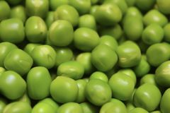 A group of green peas stacked together. stock photos