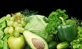 Group of green vegetables and fruits at the bottom horizontal view on black Royalty Free Stock Images